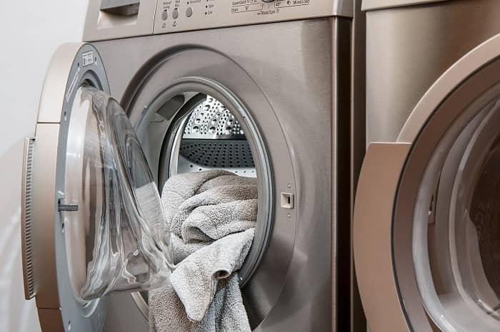 Eine Waschmaschine steht geöffnet mit einem Handtuch darin im Raum