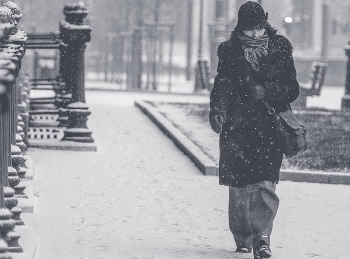 Fraun geht bei Schneefall, dick eingepackt einen Gehweg entlang