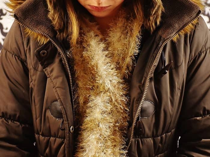 Eine Frau mit brauner Winterjacke und einem beigen Schal ist zu sehen