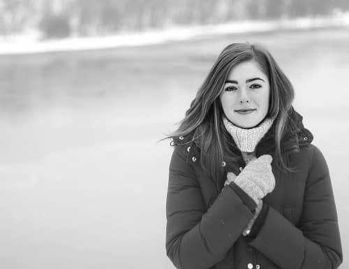 Frau steht mit Winterjacke im Freien an einem Fluss