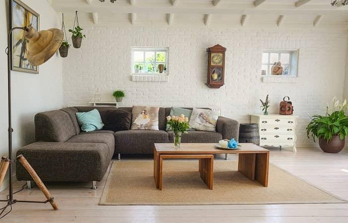 Ein skandinavischer Wohnraum, braune Couch, beiger Teppich und Boden sowie Naturmaterialien