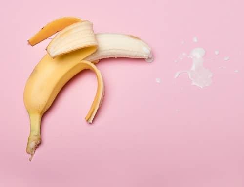Halb geschälte Banane, die einen weißen Saft verspritzt