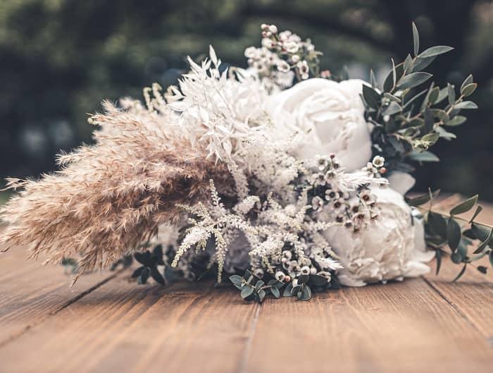 Ein Brautstrauß aus weißen Blumen und Gräsern