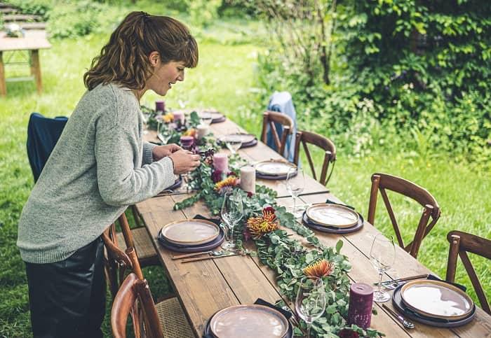 Franziska Braun dekoriert gerade einen alten Holztisch mit Blumendekoration