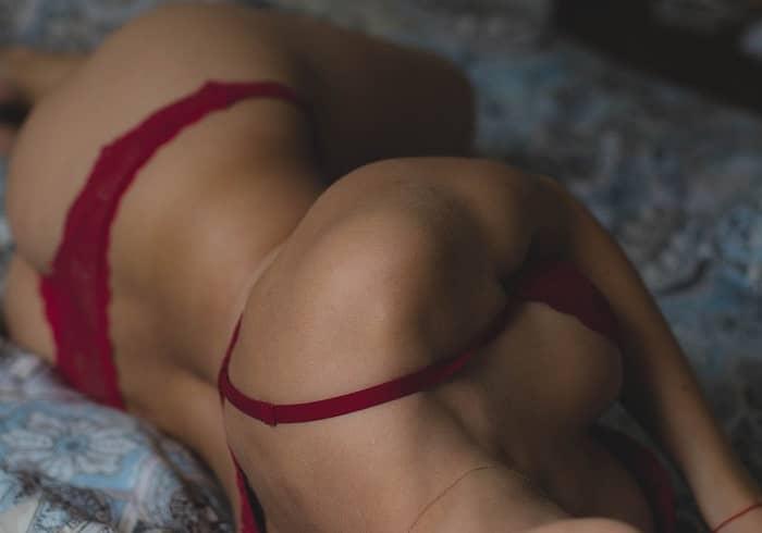 Nackte Frau mit roter Unterwäsche liegt erotisch auf einem Bett