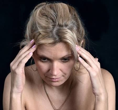 Frau sitzt traurig und einsam da