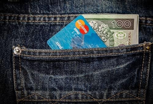 In der Gesäßtasche einer Jeans steckt Bargeld und eine Master Card