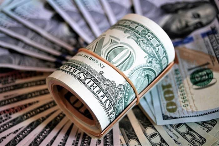 Eine große Menge Dollarnoten und ein gerolltes Bündel von Dollarscheinen