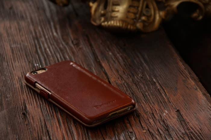 Ein Handy mit brauner Schutzhülle liegt auf einem braunen Holztisch