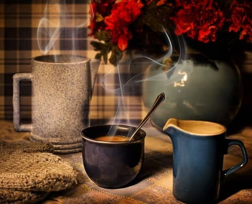 Gemütlicher Küchentisch mit Kaffeetassen und einer Vase mit roten Blumen
