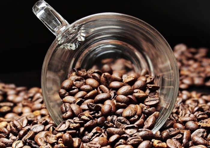 Eine Glastasse liegt in einem großen Berg Kaffeebohnen