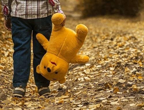 Kind geht traurig mit seinem Teddy auf einem Waldweg