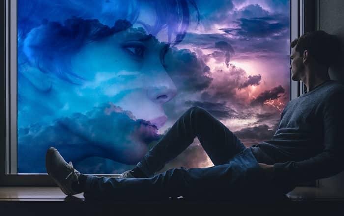 Mann sitzt auf der Fensterbank, sieht hinaus in die Wolken und sieht dort ein Frauengesicht