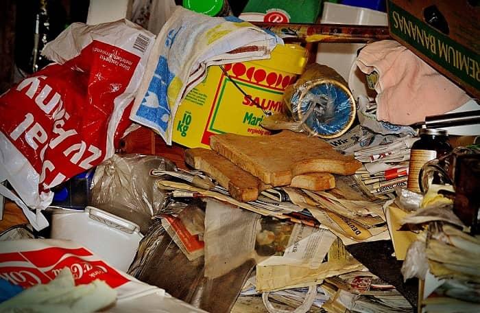 Anblick auf eine Messi Ecke, unordendlich gestappeltes Zeug, Plastikeimer, Zeitungen, Toastbrote usw.