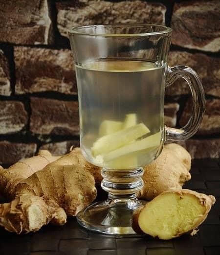 Ein Glas Tee mit frischem Ingwer darin, steht auf einem Tisch