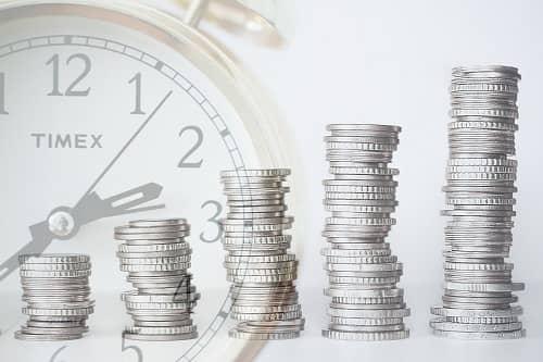 Gestapelte Geldmünzen vor einer Uhr