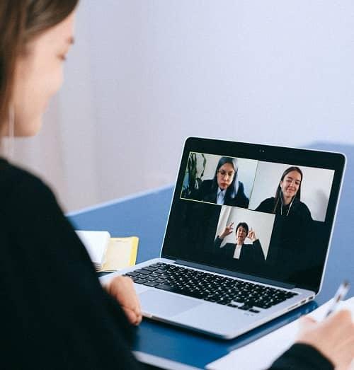 Frau sitzt vor einem Laptop in einer Videokonferenz und hat drei Teilnehmer auf dem Bildschirm
