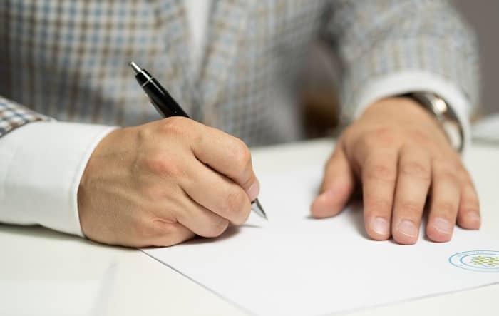 Ein Mann im Anzug unterschreibt einen Vertragt