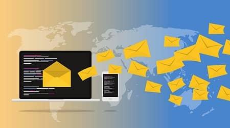 Ein Laptop mit Smartphone daraus fliegen Emails in Form von Briefkuveren