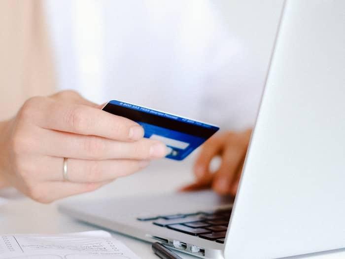 Frau sitzt vorm Laptop und bezahlt dabei mit Kreditkarte