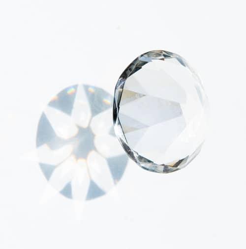 Ein weißer durchsichtiger Diamant mit Schattenwurf auf eine weiße Wand
