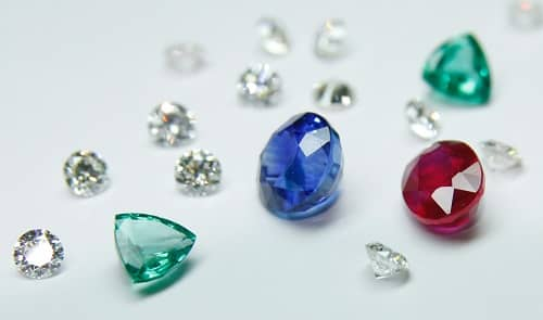 Verschieden farbige und unterschiedlich geschliffene Diamanten liegen auf einem weißen Tisch