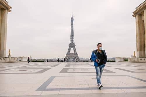 Ein Urlauber geht über einen großen Platz im Hintergrund sieht man den Eiffelturm