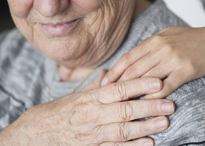 Ältere Frau legt Ihre Hand auf die Hand Ihrer Pflegerin