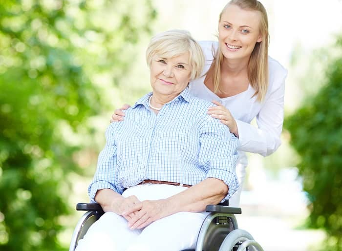Frau im Rollstuhl wird von Ihrer Pflegerin im Park begleitet