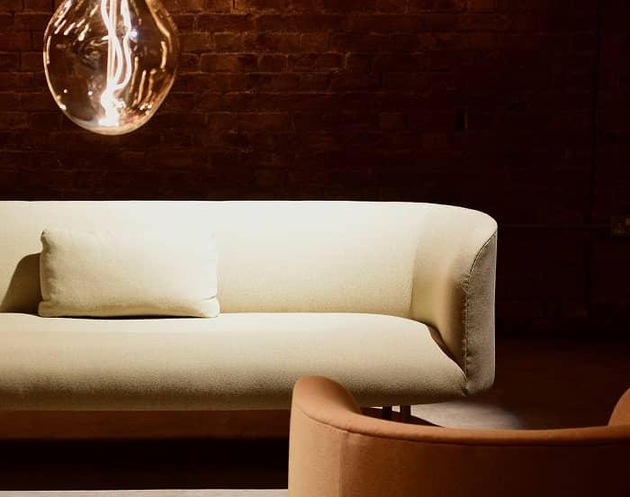 Sofa steht vor einer rozten Ziegelwand in warmen Licht