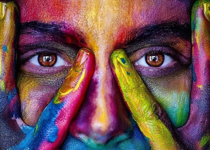 Eine Frau mit einem total bunten Gesicht, umrahmt von Ihren Händen ebenfalls in bunter Farbe
