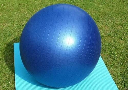 Ein großer blauer Gymnastikball liegt auf einer Yogamatte im Garten