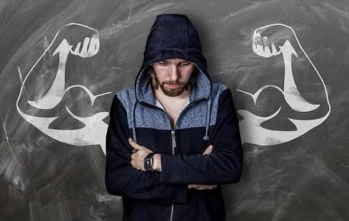 Junger schlanker, schmaler Mann steht traurig vor einer Tafel, auf die sehr muskulöse Oberarme gezeichnet sind