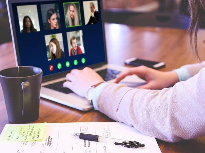 Frau sitzt vor einem Laptop und hat gerade eine Videokonferenz mit 5 Personen