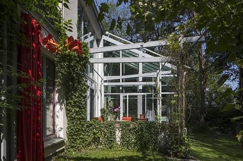 Eine große Terrasse mit Glas und weißem Aluminium überdacht