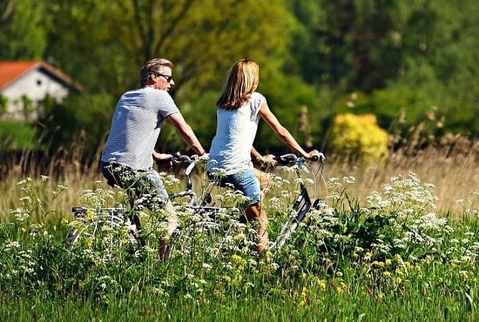 Ein Paar radelt bei Sonnenschein durch ein grüne Landschaft