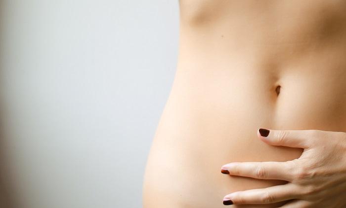 Frau hält sich den Bauch