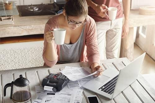 Junge Frau sitzt vor einem Laptop mit einer Tasse Kaffee und macht Buchhaltung
