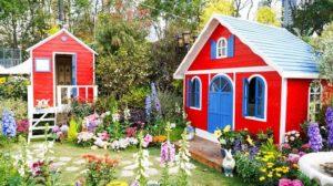 2 rote Gartenhäuschen stehen in einem bunten Blumengarten