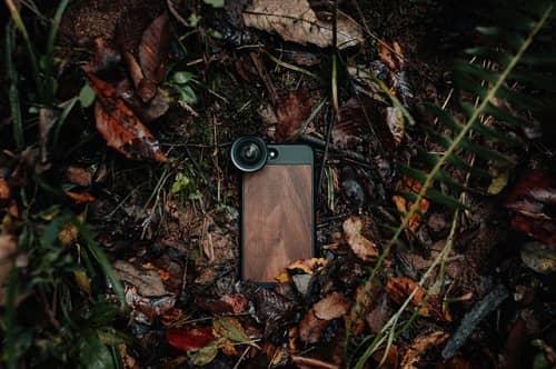 Ein Handy mit stabiler Hülle liegt am Boden im nassen Laub