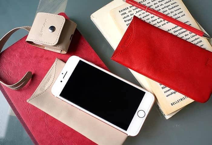 Auf einem Tisch liegt ein weißes Handy und rote Büro Utensilien sowie ein Buch
