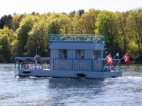 Ein kleines Hausboot mit verschiedenen Flaggen fährt auf einem Fluss