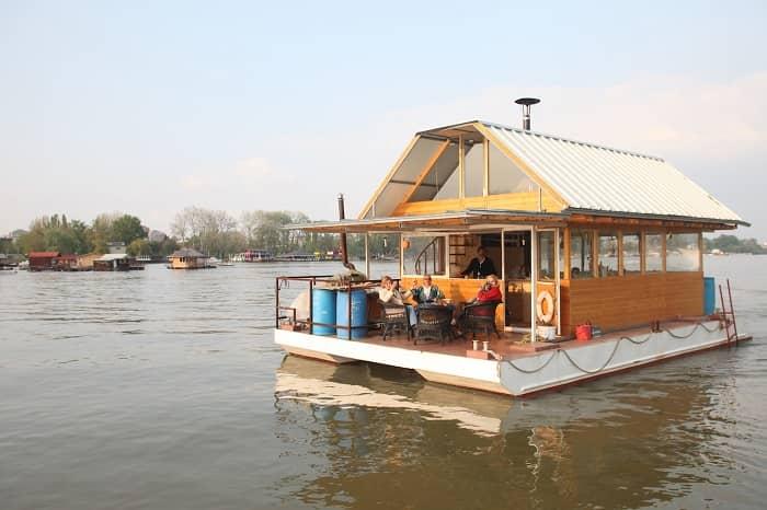 Personen sitzen auf der Terasse eines großen Hausboots