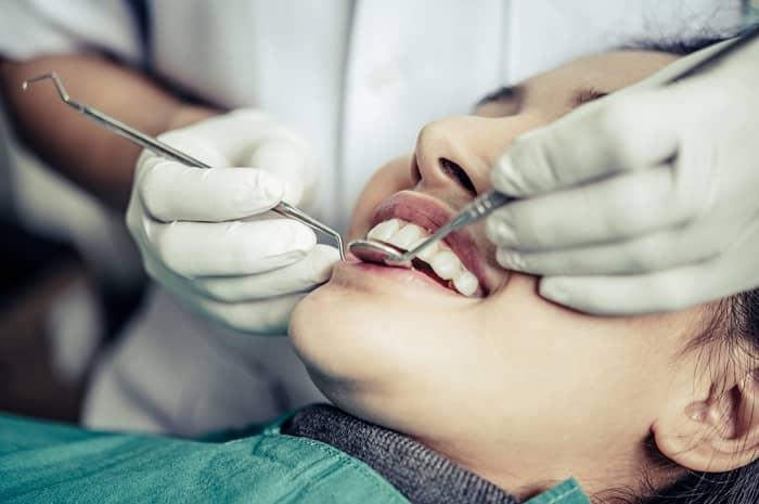 Eine junge Frau wird vom Zahnarzt in der Praxis behandelt