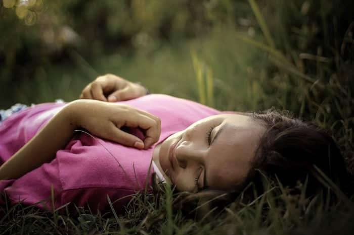 Frau liegt entspannt im Gras und schläft