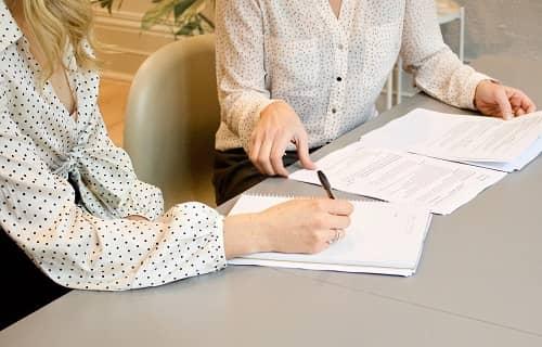 Zwei Frauen sitzen mit Papieren an einem Tisch und besprechen einen Text