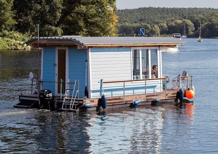 Ein weiß/blaues Hausboot schippert über einen See
