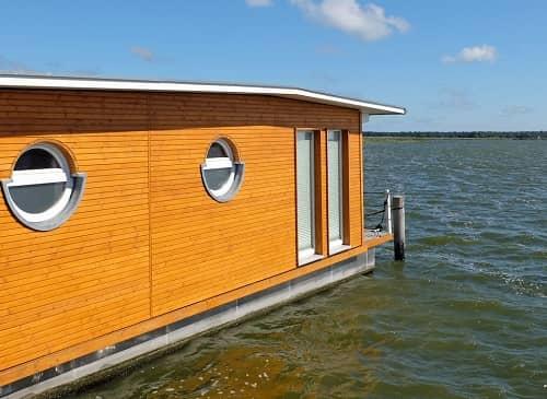 Ein großes beigefarbenes Hausboot liegt am Ufer