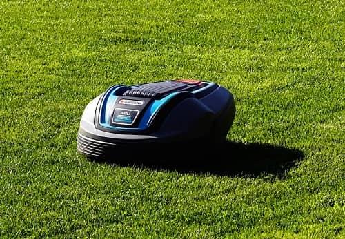 Ein Mähroboter von Gardena fährt gerade über einen schönen Rasen.