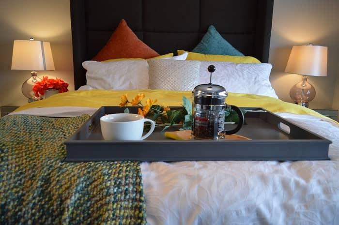 Ein dekoratives Bett, mit einem Tablett und Frühstück darauf